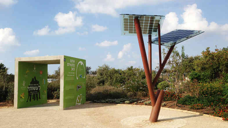 A solar power tree, invented by Michael Lasry, stands at the edge of natural greenery.