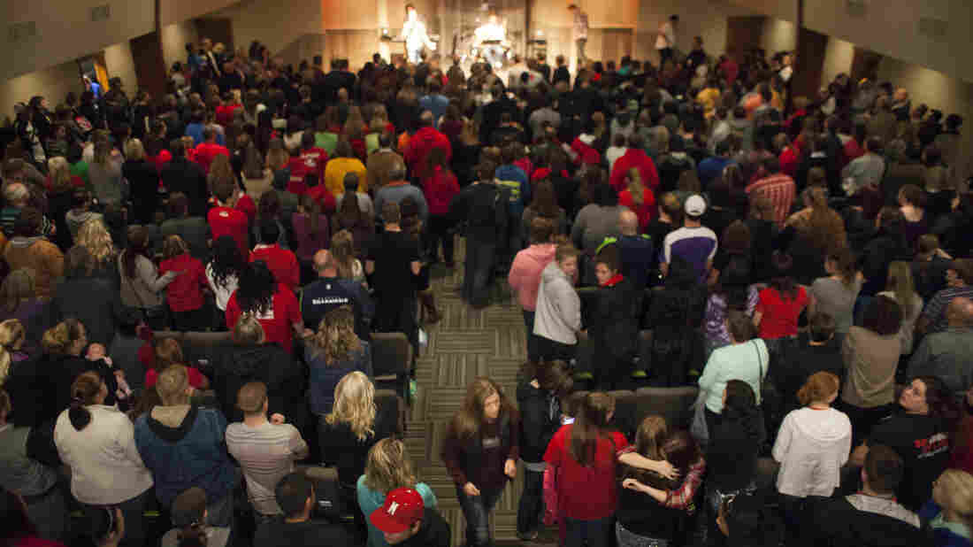 Community members and students from Marysville-Pilchuck High School gather for a vigil at the Grove Church in Marysville, Wash., Friday night. Two students died in the violence, including the gunman. Several more were wounded.