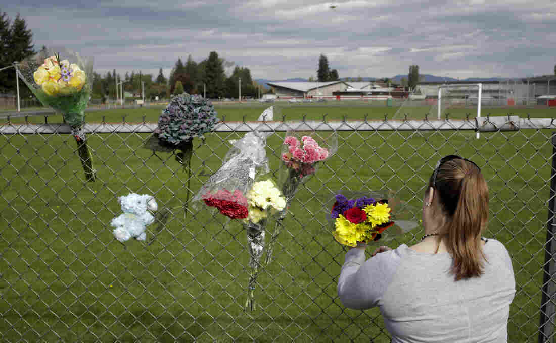 A visitor leaves flowers on Saturday, the day after a shooting at Marysville-Pilchuck High School in Marysville, Wash.