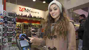 A customer makes a purchase using Apple Pay on her iPhone 6 at a Walgreens store in Times Square last Monday. The mobile payment service