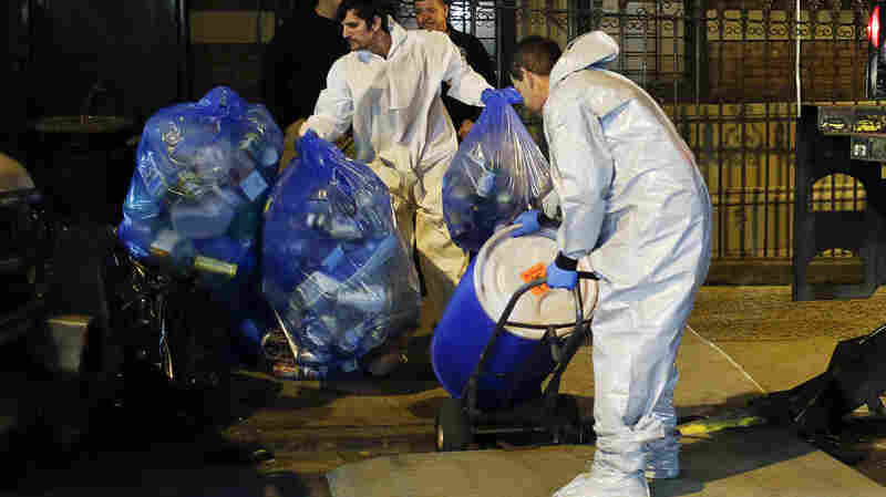 Members of a cleaning crew clear the New York apartment of Dr. Craig Spencer, who has been diagnosed with Ebola, on Friday.