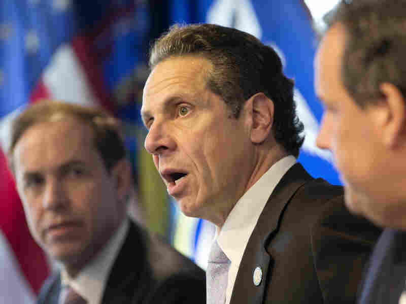 "New York Governor Andrew Cuomo (center) speaks at a news conference on Oct. 24, 2014 in New York, announcing a mandatory quarantine for people returning to the United States through airports in New York and New Jersey who are deemed ""high risk."""