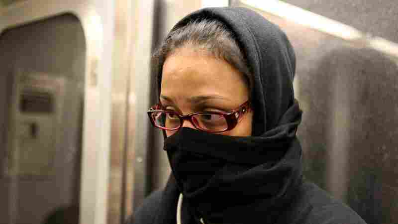 A woman on the L train in New York City last week covers her face, fearful because a doctor with Ebola rode the train days earlier. Epidemiologists say people on the subway were not at risk.