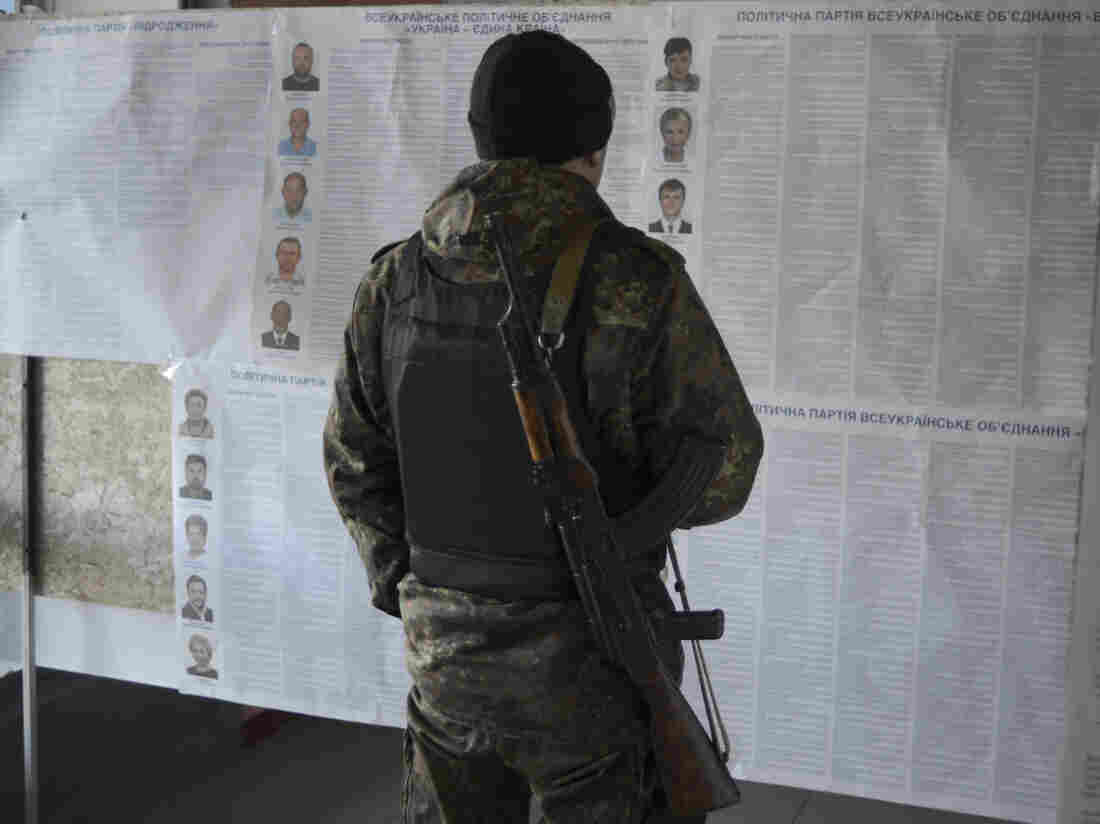 A Ukrainian government forces member, who takes part in a military operation eastern regions of Ukraine, reads candidate information sheets during a parliamentary election at a polling station in Novoaidar near Luhansk, on Sunday.
