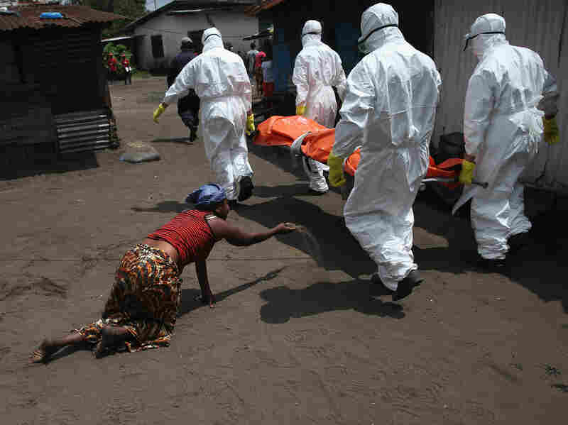 As an Ebola burial team takes Mekie Nagbe, 28, for cremation, her sister throws a handful of soil toward the body — a parting gesture.