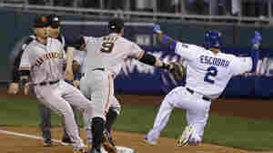 The San Francisco Giants' Brandon Belt can't reach the Kansas City Royals' Alcides Escobar as he slides safely to first base on an infield single Tuesday night during the second inning of Game 6 of baseball's World Series in Kansas City, Mo. Escobar eventually would score the Royals' fourth run.