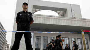 Police officers stand guard in front of the Hefei City Intermediate People's Court in China's Anhui Province.