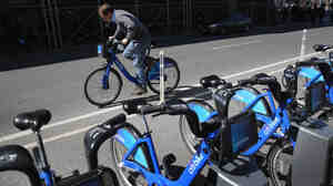 A Citi Bike user pedals off from a bicycle station. The company that owns the service in New York and other cities has been sold, after suffering problems tied to its supply chain and the weather.