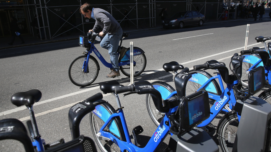 A Citi Bike user pedals off from a bicycle station. The company that owns the service in New York and other cities has been sold, after suffering problems tied to its supply chain and the weather. (John Moore/Getty Images)