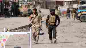 Iraqi soldiers walk in Jurf al-Sakhr, south of the capital Baghdad, on Monday after Iraqi military forces retook the area from Islamic State militants. Iraqi forces, supported by U.S. airstrikes, have made limited gains in recent months, but critics are questioning whether the U.S. strategy is likely to succeed.
