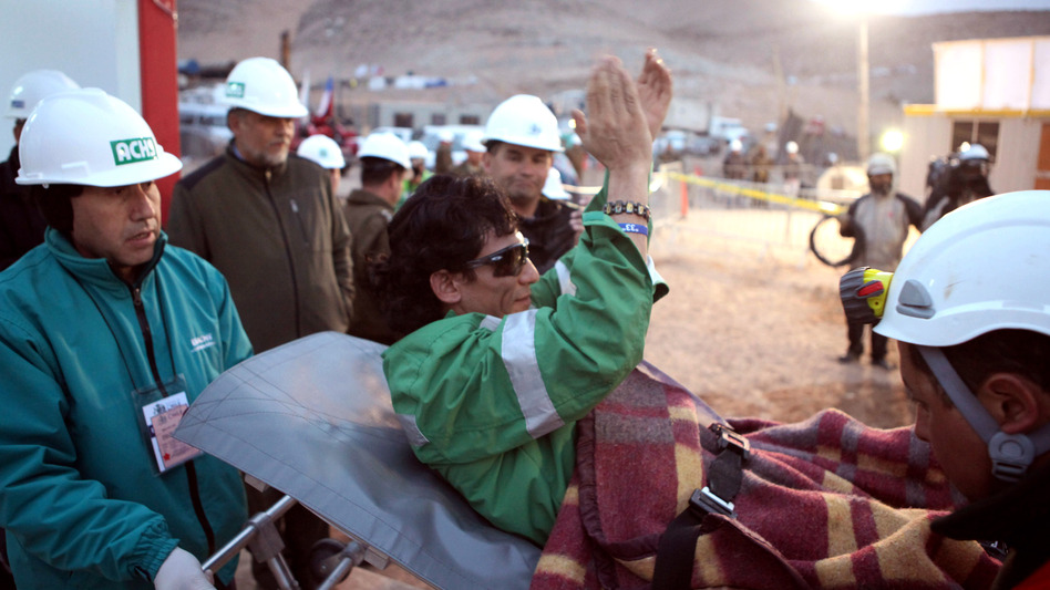 Miner Claudio Yanez applauds as he is carried away on a stretcher after being rescued from the collapsed San Jose mine where he had been trapped with 32 other miners for over two months in 2010 near Copiapo, Chile. (Hugo Infante/AP)
