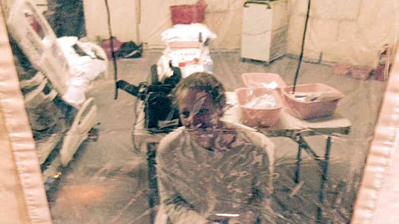 """A photo taken Sunday of Kaci Hickox in an isolation tent at University Hospital in Newark, N.J. Hickox, who was later discharged and allowed to return to her home in Maine, says she has no intention of abiding by a """"voluntary"""" quarantine there."""