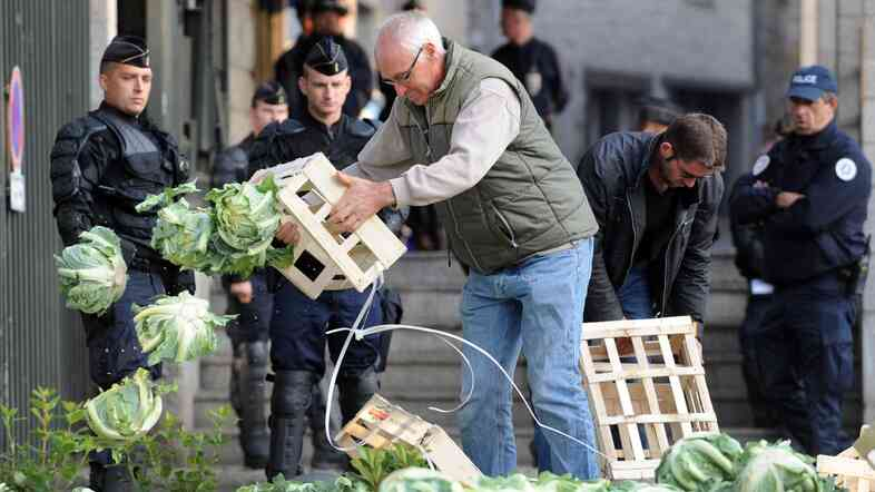 A farmer protesting falling prices dumps cauliflower in front of the prefecture building of Saint-Brieuc in northwestern France, as police look on Sept. 24.