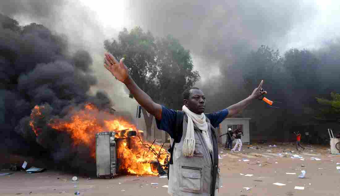 Demonstrators set fire to cars near Burkina Faso's Parliament on Thursday in Ouagadougou.