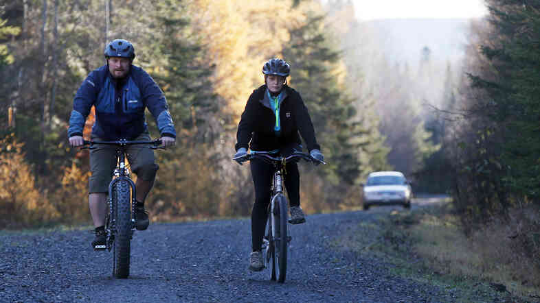Nurse Kaci Hickox and her boyfriend, Ted Wilbur, are followed by a Maine State Trooper as they ride bikes on a trail near her home in Fort Kent, Maine, on Thursday.
