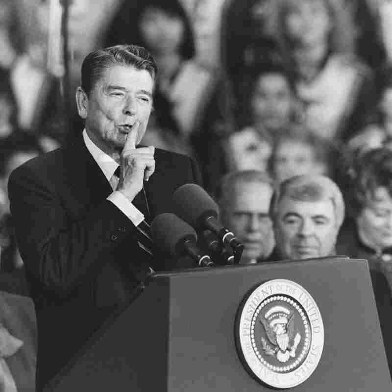 U.S. President Ronald Reagan quiets a cheering crowd at a Republican rally in November 1986.
