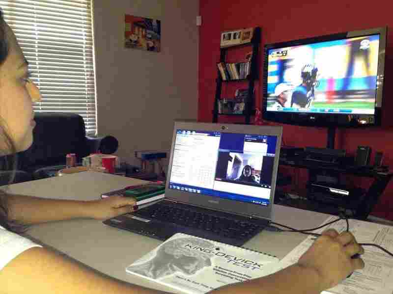 Dr. Amaal Starling, a neurologist from the Mayo Clinic in Arizona, watches a Northern Arizona University football game via both VGo and live television.