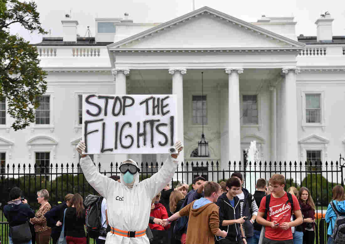 A protester outside the White House demands a halt to all flights to the United States from West Africa.