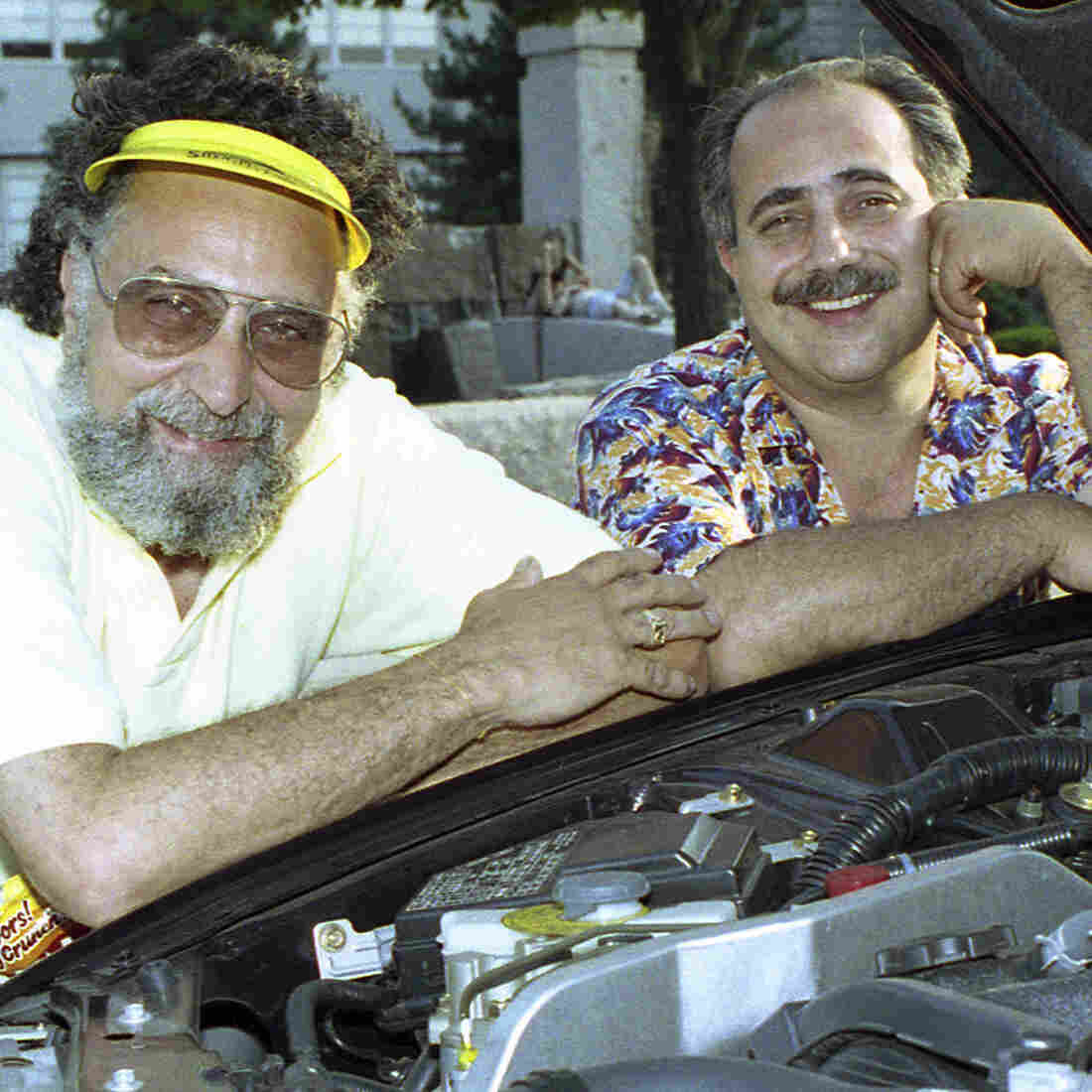 Brothers Tom (left) and Ray Magliozzi pose under a car hood in Boston. The comic duo hosted NPR's Car Talk for a quarter of a century before retiring in 2012. Since then, the show has been heard in reruns. Tom has died at age 77.