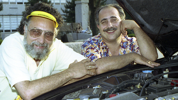 Brothers Tom (left) and Ray Magliozzi pose under a car hood in Boston. The comic duo hosted NPR's Car Talk for a quarter of a century before retiring in 2012. Since then, the show has been heard in reruns. Tom has died at age 77. (AP)