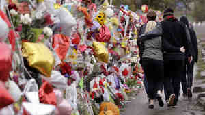 People walk arm-in-arm Thursday past a memorial for victims outside a school following a deadly shooting there nearly a week earlier in Marysville, Wash.