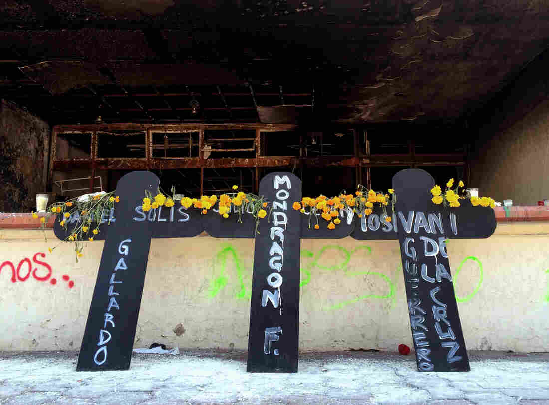 Three large crosses lean against the burned out facade of Iguala's City Hall. Masked protesters angry about the disappearance of 43 students — attacked on orders of Iguala's mayor, according to Mexican federal authorities — burned the building last week.