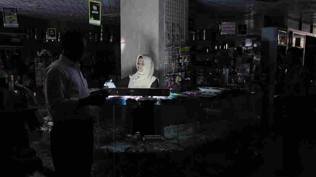 A customer walks past a sales counter in a shopping mall during a blackout in Dhaka, Bangladesh, Saturday. Bangladesh was hit by a nationwide blackout on Saturday after a transmission line bringing electricity from neighboring India failed.