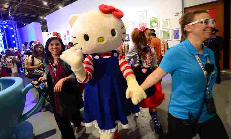 A person dressed in a Hello Kitty costume is led through the hall greeting visitors attending the Hello Kitty Convention in the Little Tokyo district near downtown Los Angeles Friday.
