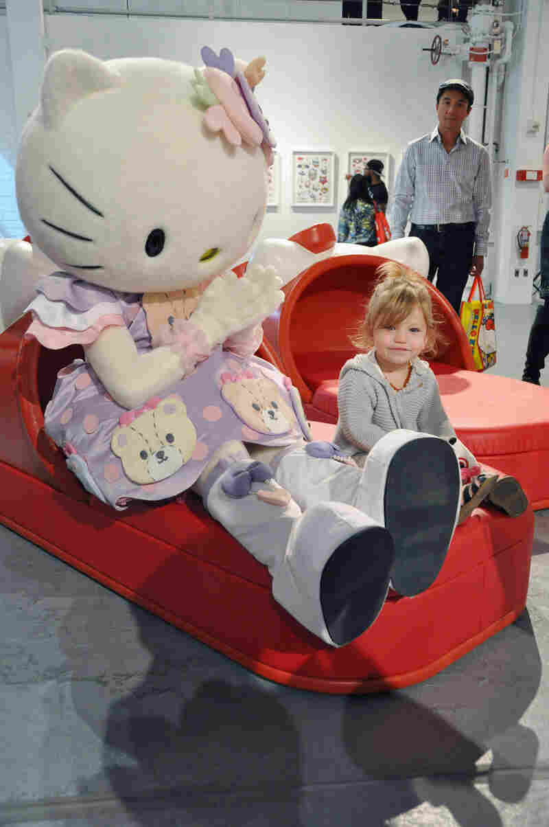 A girl sits by Hello Kitty at the Museum of Contemporary Art in Los Angeles on Oct. 29, 2014, when guests were invited to the first-ever Hello Kitty Convention to celebrate Hello Kitty's 40th birthday.