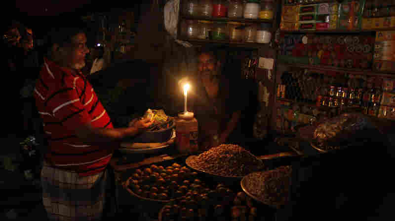 A man sells products by candlelight at a grocery during a blackout in Dhaka, Bangladesh, on Saturday.
