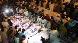 Locals crowd around the bodies of victims from a suicide bomb attack, at a hospital in Lahore on Sunday.