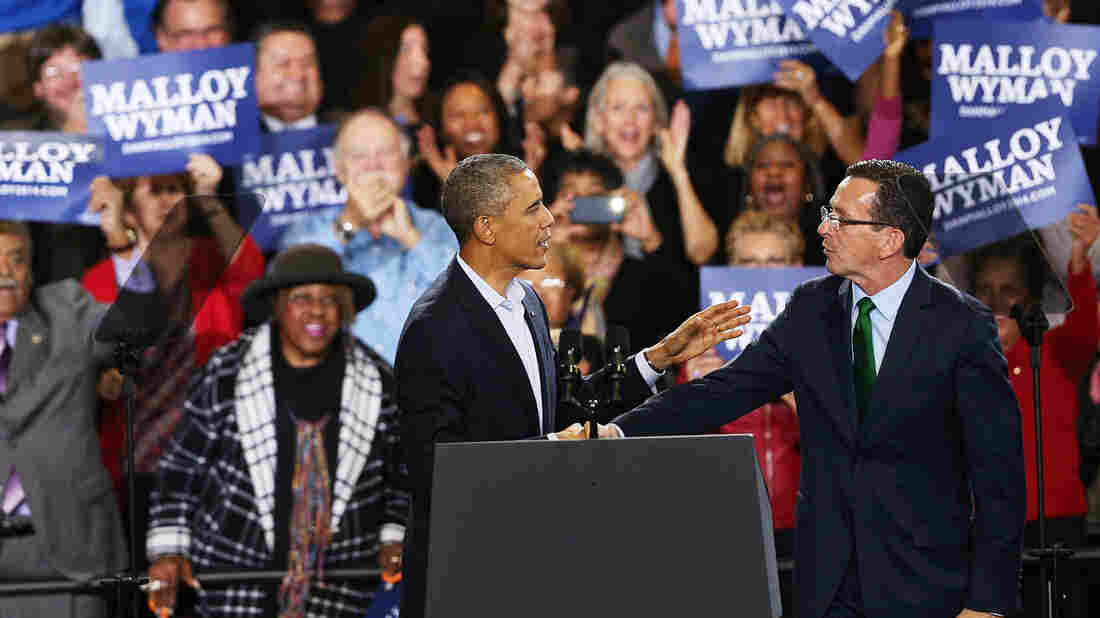 President Obama stands with Connecticut Gov. Dan Malloy in Bridgeport on Sunday. Malloy is in a tough re-election battle with Republican Tom Foley. The president spent the weekend trying to energize the Democratic base to get out and vote in Tuesday's midterm elections.