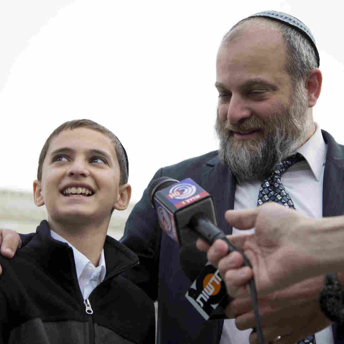 Menachem Zivotofsky and his father, Ari Zivotofsky, gather to speak to media outside the Supreme Court in Washington on Monday. The court is taking its second look at a dispute over the wording of U.S. passports for Americans born in Jerusalem, a case with potential foreign policy implications.
