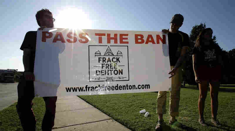 From left, Topher Jones, Edward Hartmann and Angie Holliday hold a campaign sign outside City Hall in Denton, Texas, on July 15, 2014. Voters in the college town approve a ban on fracking on Tuesday.