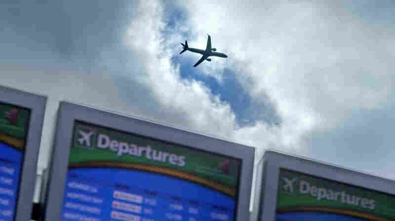A plane takes off over a departure board at Hartsfield-Jackson Airport in Atlanta last November. Airlines say they expect an uptick in Thanksgiving travel this year.