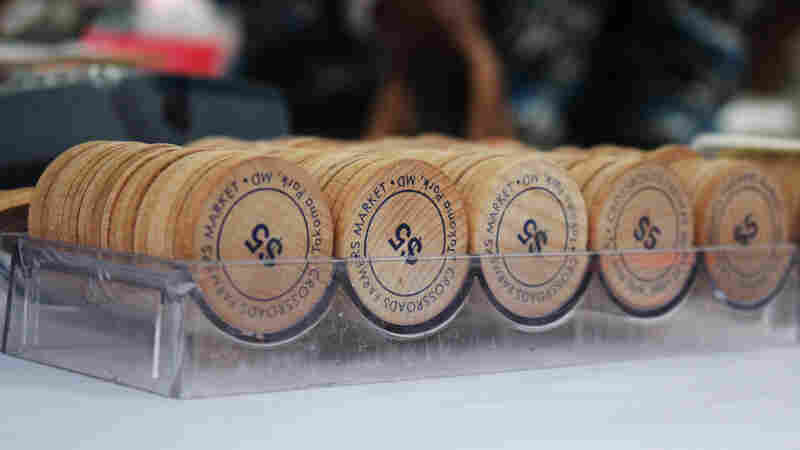 "These wooden tokens are handed out to shoppers who use SNAP benefits to purchase fresh produce at the Crossroads Farmers Market near Takoma Park, Md. Customers receive tokens worth twice the amount of money withdrawn from their SNAP benefits card — in other words, they get ""double bucks."""