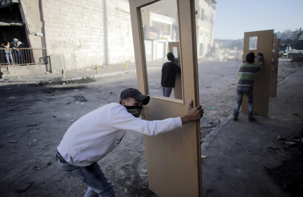Palestinian stone-throwers take cover behind doors during clashes with Israeli police in Jerusalem on Thursday. For months, the streets of East Jerusalem have been tense, with frequent clashes between police and Palestinians.