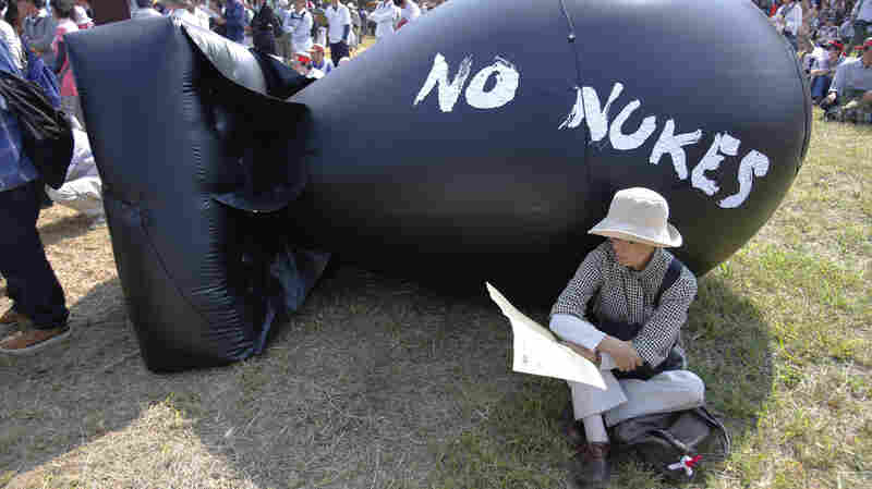 An anti-nuclear protester rests in front of bomb-shaped balloon during a rally against Japanese nuclear plants in Tokyo, back in September.