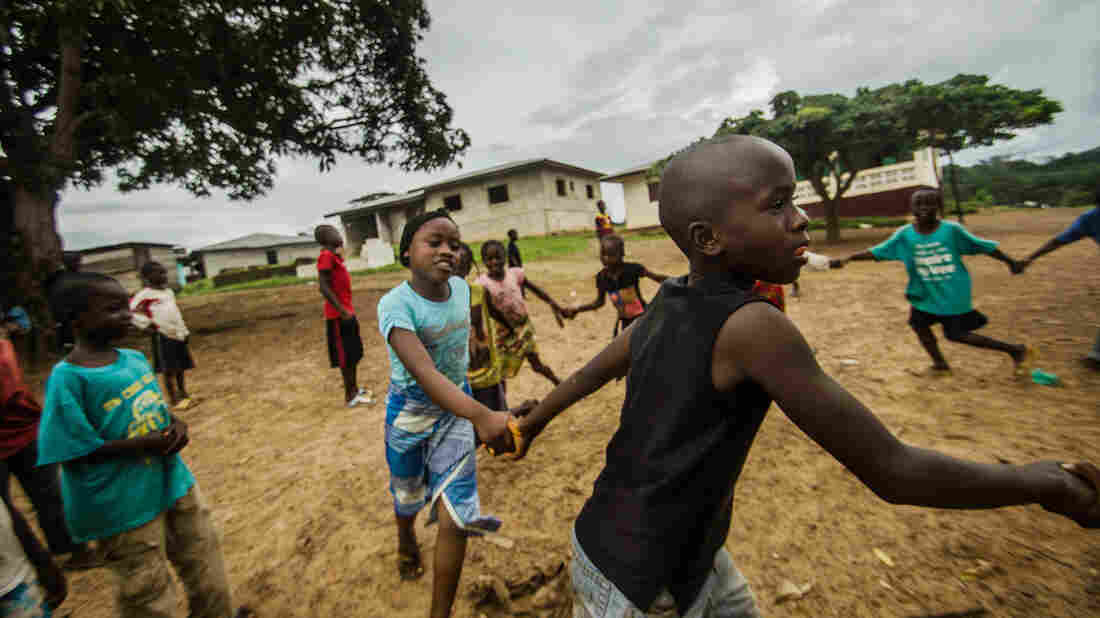 Mariama and Fomba Kanneh play in an open space in Barkedu, Liberia. With schools closed across the country, many kids spend their time playing outside every day.
