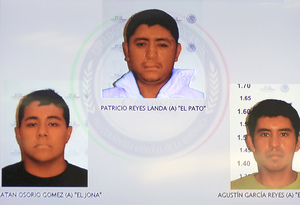 Pictures of the detainees for the case of missing students are seen displayed on a television screen during a news conference at the Attorney General's Office building in Mexico City on Friday.