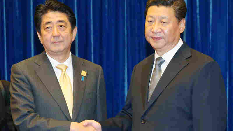 Japanese Prime Minister Shinzo Abe (left) and Chinese President Xi Jinping shake hands at the Great Hall of the People in Beijing on Monday, prior to their first-ever talks.