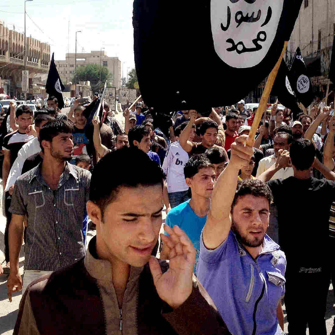 Demonstrators chant in favor of the Islamic State and carry the group's flags in Mosul, Iraq, in June. With videos, Internet magazines and social media, the group has effectively recruited throughout the world.