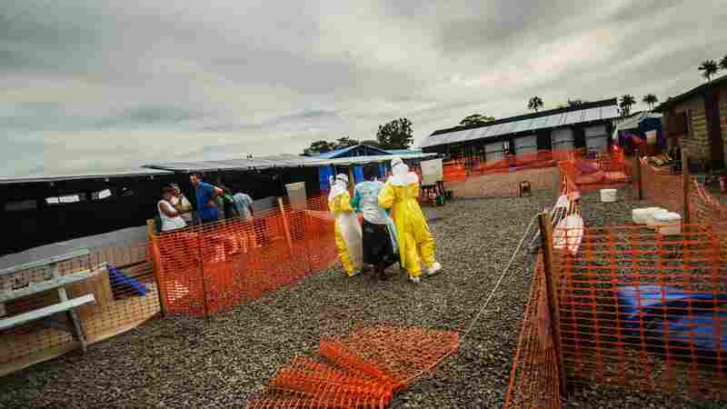 Nurses assist a new patient at an Ebola center in Liberia's Lofa County. As drug trials get underway, patients may receive experimental medicines.