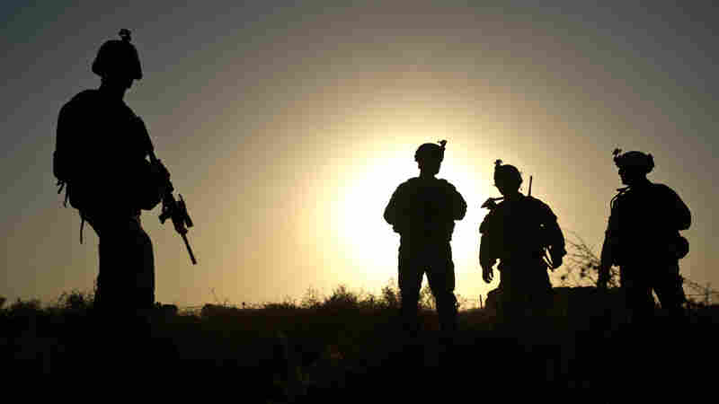 """U.S. soldiers stand at a checkpoint around Lakokhel camp in Afghanistan in 2010. Many soldiers return from war suffering from """"moral injuries,"""" or dealing with the fact that their sense of right and wrong was violated."""