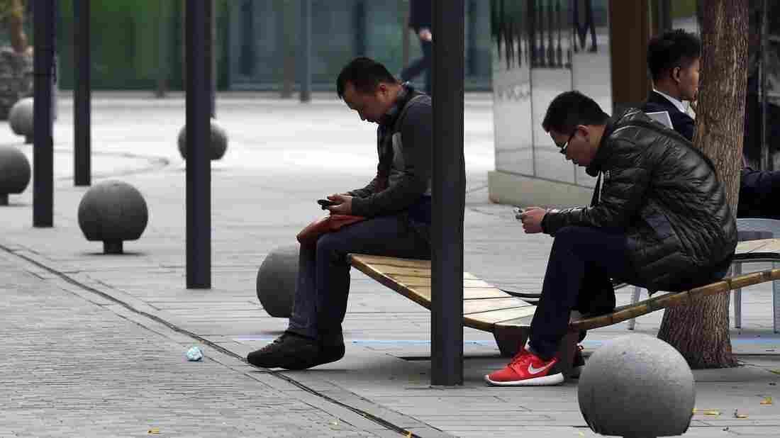 An international tariff on high-tech goods could be rewritten, thanks to negotiations in China. Here, men use smartphones in Beijing last month, days after Apple released its iPhone 6 in the Chinese market.
