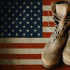 Grunge U.S. Army boots on sandy american flag background collage