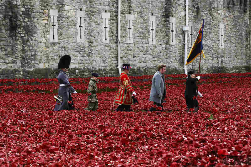 "Servicemen and artist Paul Cummins (second from right) walk past his art installation ""Blood Swept Lands and Seas of Red,"" made of ceramic poppies, during an Armistice Day ceremony at the Tower of London on Tuesday."