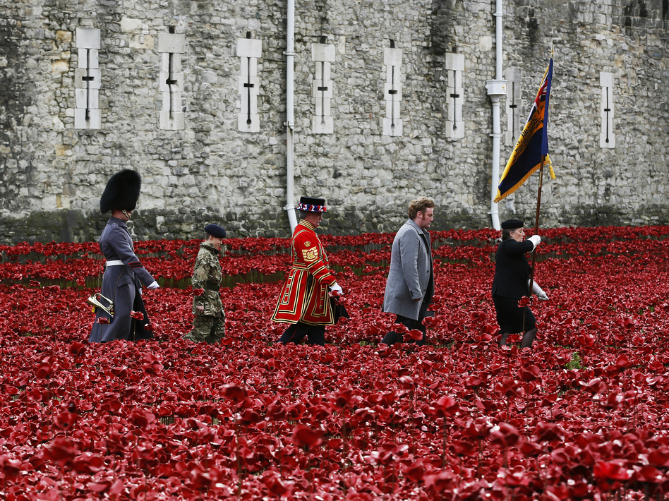 "British servicemen and artist Paul Cummins (second from right) walk past his art installation ""Blood Swept Lands and Seas of Red,"" made of ceramic poppies, during an Armistice Day ceremony at the Tower of London on Tuesday. (Stefan Wermuth/Reuters/Landov)"