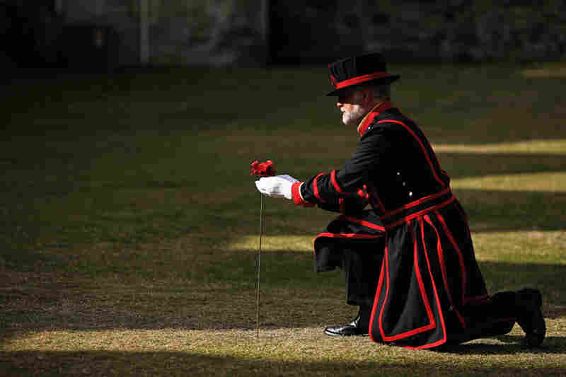 Crawford Butler, the longest-serving Yeoman Warder at the Tower of London, plants the first ceramic poppy in the dry moat at Tower of London on July 17.