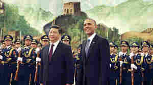 U.S. President Barack Obama, right, smiles after a group of children waved flags and flowers to cheer him during a welcome ceremony Wednesday with Chinese President Xi Jinping at the Great Hall of the People in Beijing. In a surprise agreement late Tuesday, China agreed to a first-ever target for capping its carbon emissions, while the United States pledge to cut faster than previously planned.